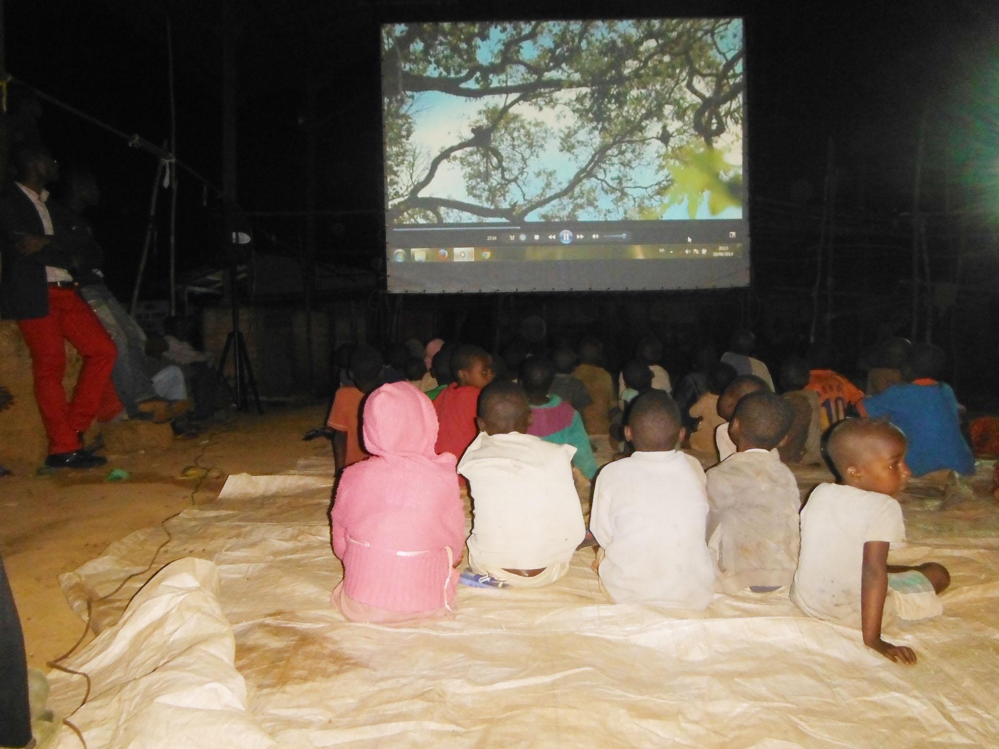 Les enfants émerveillés face à une projection grand écran au village